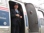 Amtrak Downeaster conductor standing in Amfleet car doorway, as the Downeaster train leaves Durham, New Hampshire