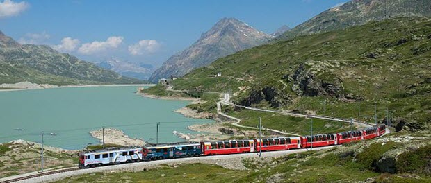 Two RhB ABe 4/4III multiple units with a Bernina Express train on the Bernina line, passing Lago Bianco by Kabelleger / David Gubler via Wikimedia Commons